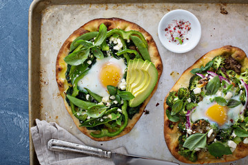 Breakfast pizza with baked egg and greens