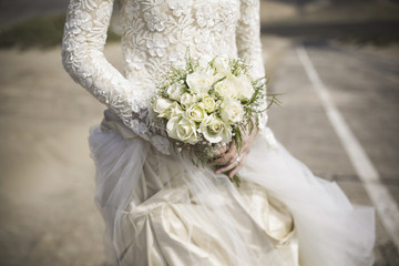 Midsection of bride holding rose bouquet outdoors