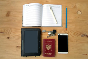 ebook, phone, passport, notebook and keys on wooden table