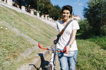 Smiling young woman pushing bicycle