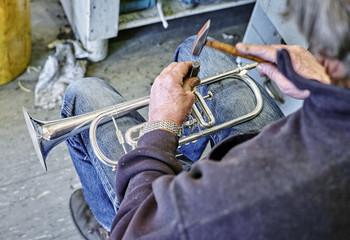 Instrument maker repairing trumpet in workshop