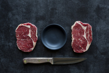 Two rib eye steaks arranged with a bowl and knife