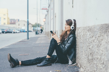 Young beautiful asiatic woman sitting on the floor listening music with earphones and smart phone hand hold - music, technology, social network concept