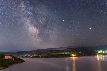 Milky way over lake Cincis in Romania with Mars and Saturn