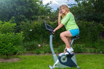 Красивая блондинка занимается спортом на велотренажере в саду и говорит по телефону