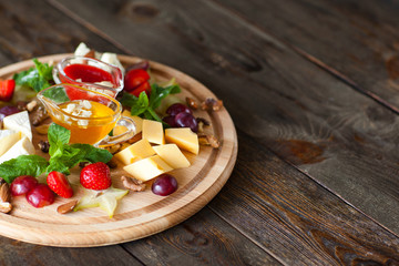 Fruit and cheese plate on wood free space. Top view on round cutting board with different kinds of cheese, fruits and nuts and two sauces. French delicatessen on dark wooden background with copyspace