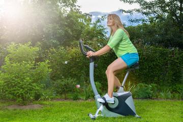 Красивая блондинка занимается спортом на велотренажере в саду