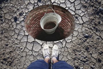 Top view of a man standing in front of built drinking water reservoir with empty metal rusty pail. Conceptual lack of drinking water.