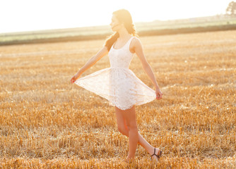 Portrait of beautiful young woman walking through a wheat field at sunset.