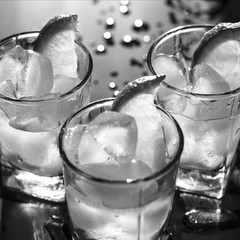 Black and white photo. Closeup of vodka with ice and lemon and lime on a black background. Reflection. Passion. Elegance