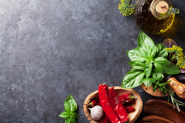 Fresh garden herbs in mortar, chili and oil