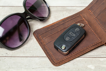 Top view of set: car keys, sunglasses on wood background