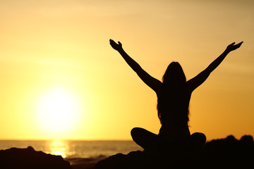 Happy woman raising arms looking at sunrise