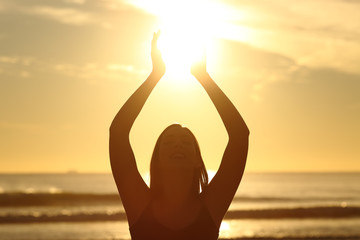 Woman holding sun at sunset