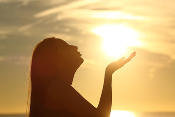 Woman silhouette kissing sun at sunset