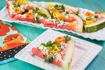 Piece of vegetarian watermelon pizza with crumbled blue cheese,