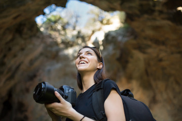 Woman traveler photographing and exploring a cave.Travel and adventure concept.Woman Caver Spelunker exploring inside of a cave.Woman holding her camera in a cave