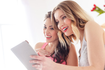 Cheerful two friends entertaining with modern technology