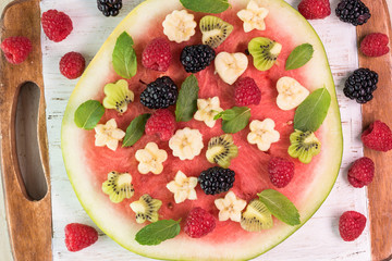 Fruit watermelon pizza with fresh berries, banana, kiwi and mint