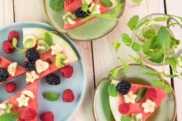 Pieces of fruit watermelon pizza with fresh berries, banana, kiwi.