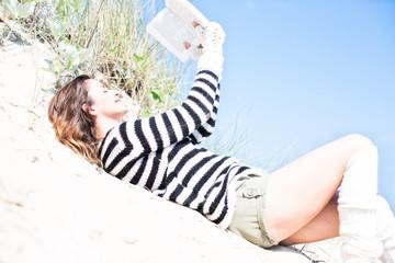 Frau liest ein Buch im Sand
