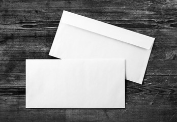 Photo of two blank envelopes on a dark wooden background. Back and front. Template for design portfolios. Mock-up for your design. Top view.