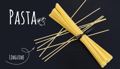 Uncooked Italian pasta Linguine on black slate stone background with white lettering, top view