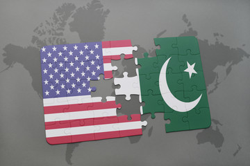 puzzle with the national flag of united states of america and pakistan on a world map background
