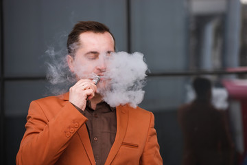 Young man smoking electronic cigarette on background of building