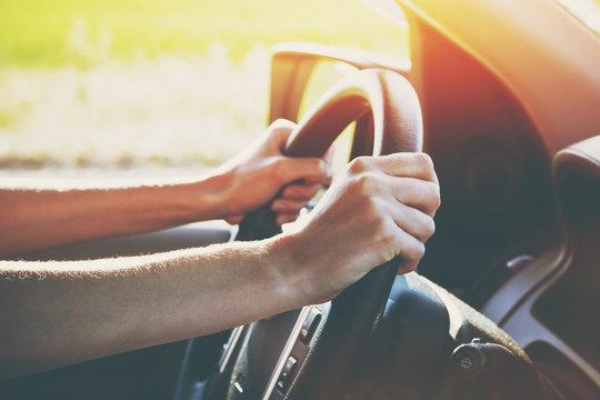 hands on steering wheel driving car