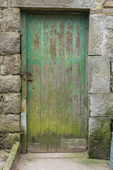 A green weathered rustic, Old wooden farm stable door, set in a stone wall