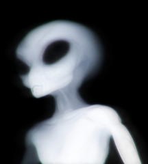 Grey alien illuminated as he passes through dimensions