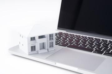 ノートパソコンと白い家の模型