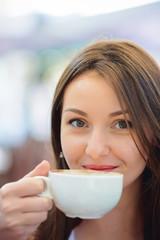 Happy woman drinking a fresh coffee cappucino