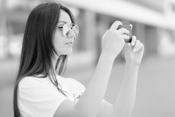 Young woman making photos with smartphone camera