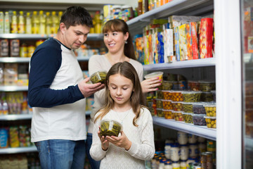 Happy young parents with little girl buying tinned