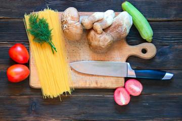 porcini, spaghetti, tomatoes, zucchini, parsley, knife on dark w