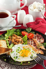 English breakfast with bacon, fried egg and beans