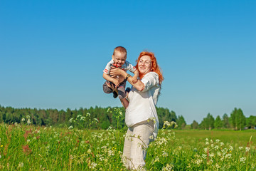 Beautiful red-haired mother playing with her baby in the field.
