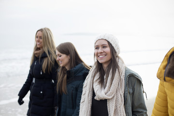 Group Of Female Friends Enjoying Winter Walk On Beach