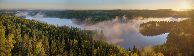 Sunrise panorama landscape at Aulanko nature park in Finland. Fog rising from the lake on misty summer morning.