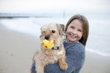 Young Girl Playing With Pet Dog And Ball On Beach