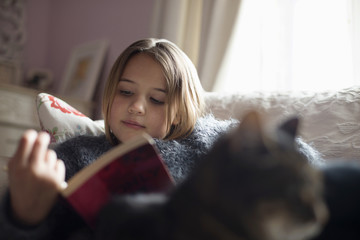 Girl reading book while sitting on sofa with cat