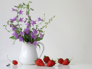 Bouquet of purple bells flowers in a vase and strawberries. Home decoration with violet flowers in a vase and fresh strawberries. Romantic floral still life with campanula flowers and red fruits.