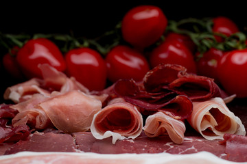 Jambon mix. Ham. Traditional Italian and Spanish salting, smoking, dry-cured dish - jamon Serrano and prosciutto crudo sliced with herbs and tomatos on dark stone background. Copy space. Closeup.