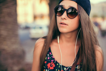 Beautiful girl listening to music. background of the street