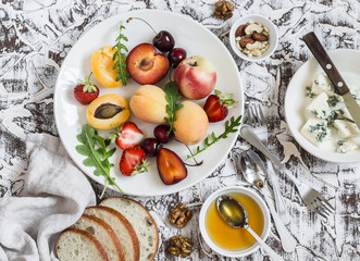 Summer fruits - apricots, peaches, plums, cherries, strawberries and blue cheese, honey, walnuts on a light stone background. Healthy, diet, vegetarian food. Delicious summer dessert or snack