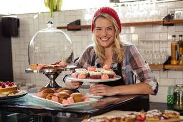 Waitress posing with cakes