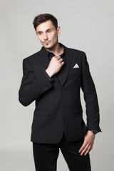 Studio portrait of handsome elegant young man in black  clothes