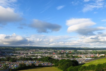 Wide angle view of Glastonbury Festival beneath sunny blue skies from a hillside